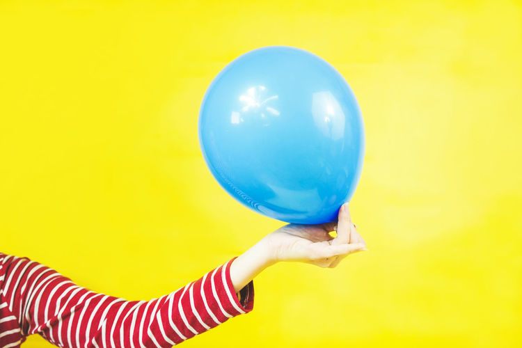 Balloon Human Hand Human Body Part Hand Holding One Person Colored Background Yellow Studio Shot Blue Striped Indoors  Women Child Single Object Childhood Body Part Offspring Adult Human Limb Inflating Stripes Vibrant Color Vibrant Party Event Celebration Chic Idea Composition Colorful Intense Intense Colors Plastic Art