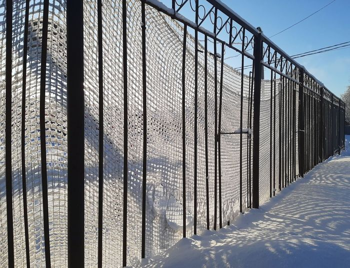 Snow covered metal fence against sky