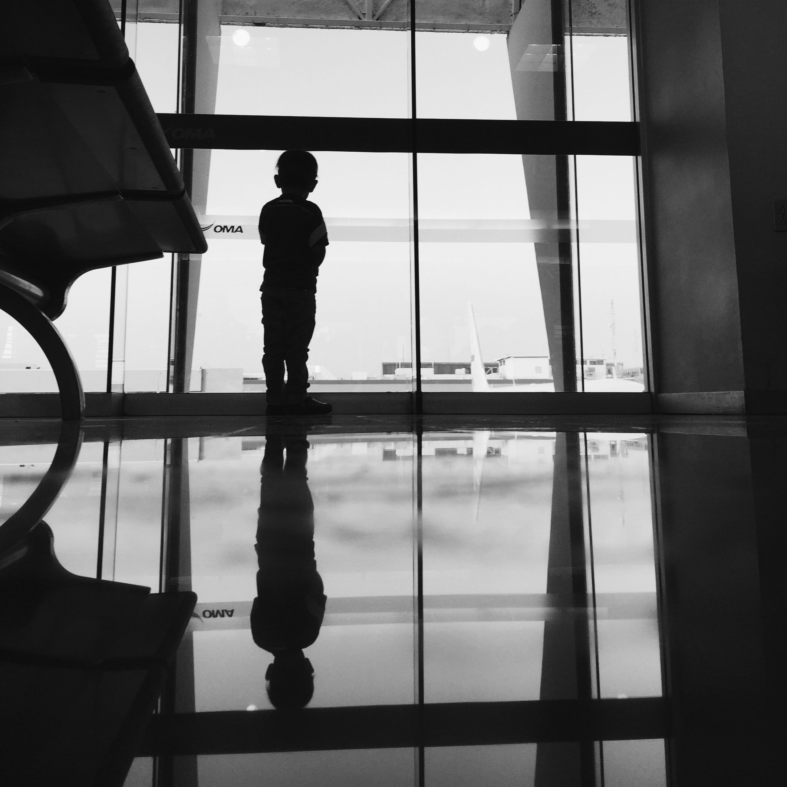 indoors, window, glass - material, transparent, reflection, glass, built structure, architecture, men, modern, day, looking through window, transportation, travel, silhouette, sky, lifestyles, sunlight, airport