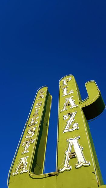 """waterless cactus ~ written by bill II """"~)) blink by bill II Architecture Blue Cactus Clear Sky Communication Day Low Angle View Metal Cact Neon Neon Sign No People Outdoor Sign Outdoors Sky Text Yellow"""