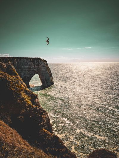 Man jumping on rock by sea against sky