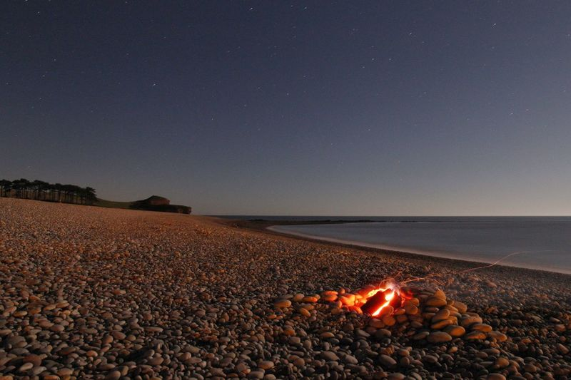 Bonfire on seashore against star field at dusk