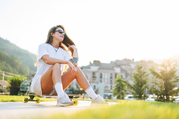 Slim young woman with long blonde hair in sports clothes with longboard in outdoor skatepark
