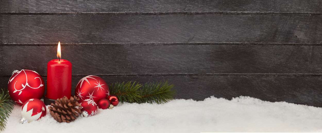 Red Christmas Baubles And Lit Candle On Snow Against Wall