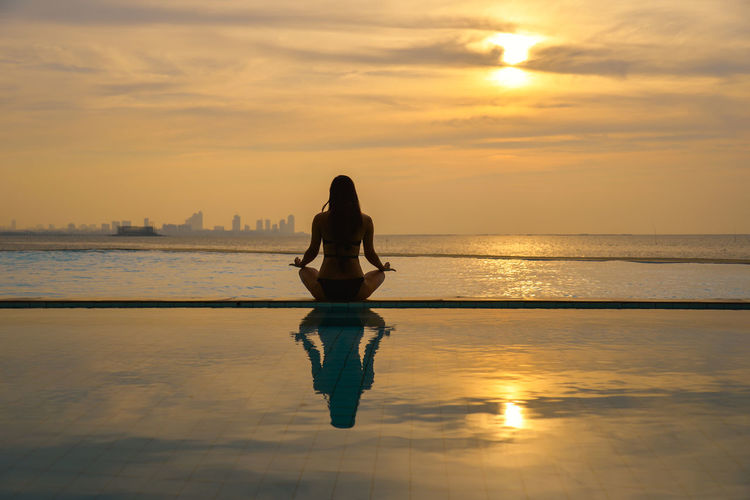 Full length of man on sea against sky during sunset