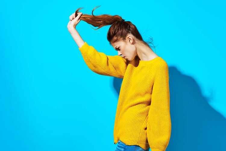 Young woman holding yellow while standing against blue background