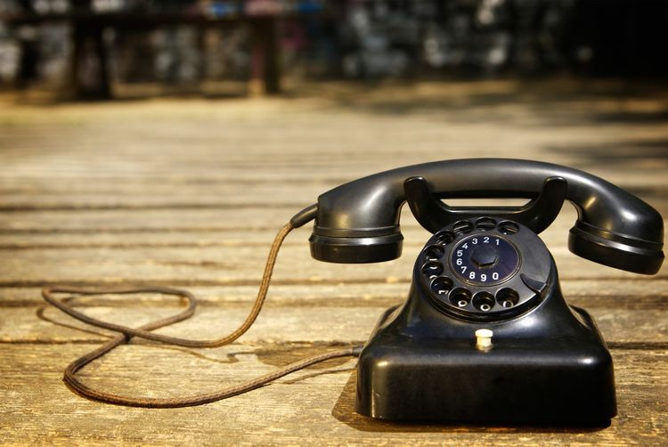 Close-Up Of Black Rotary Phone On Wooden Floor
