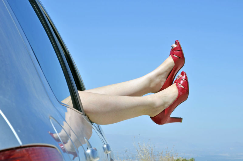 Low section of woman in car against blue sky