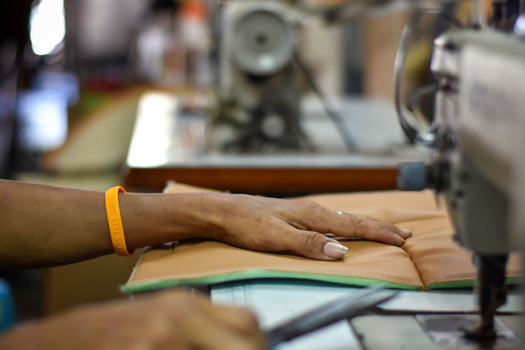 Cropped hands working on sewing machine