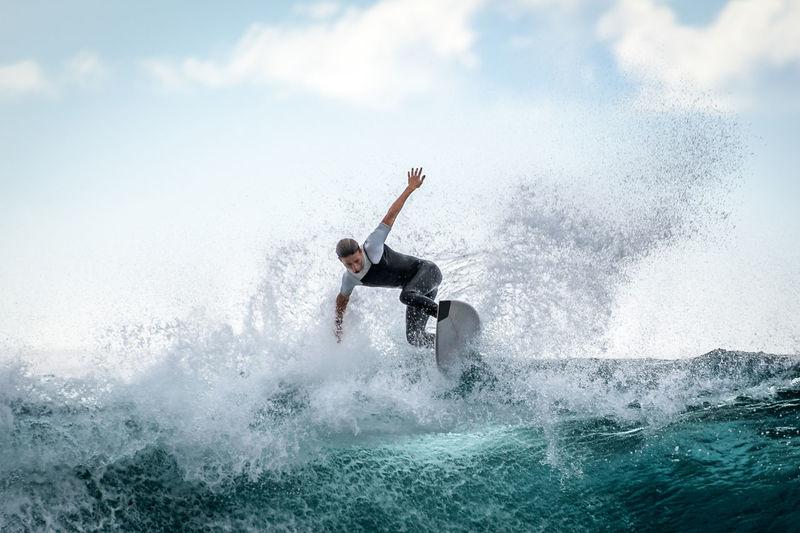 Teenager boy surfing in sea against sky