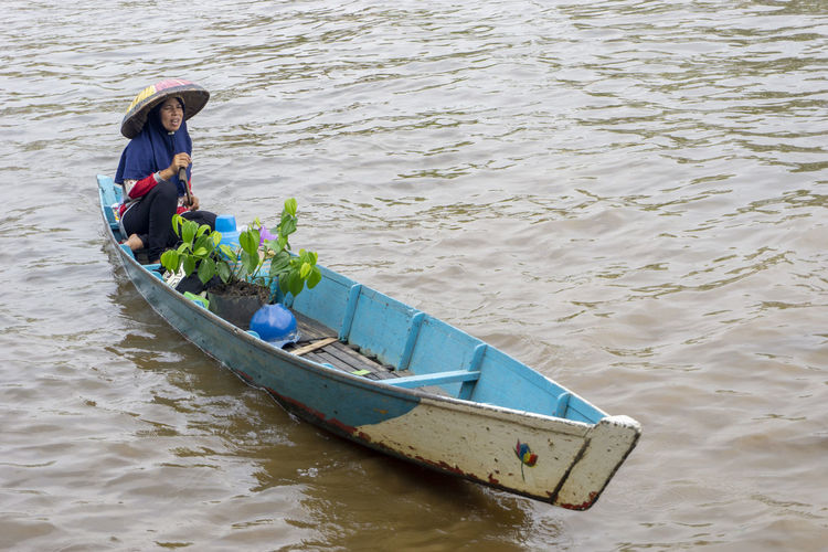High angle view of woman with plant on boat in lake