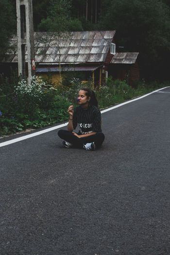 Full length of woman sitting on road