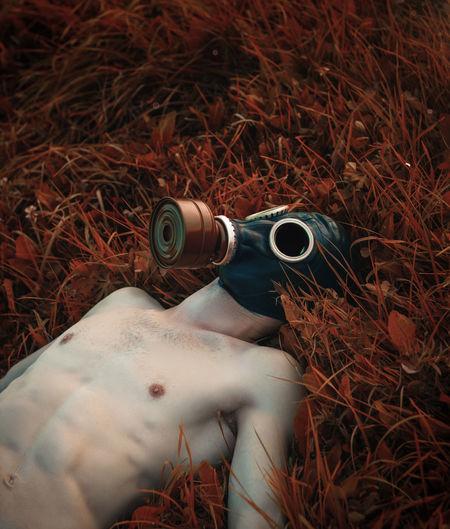 Shirtless man wearing gas mask while lying on grassy land
