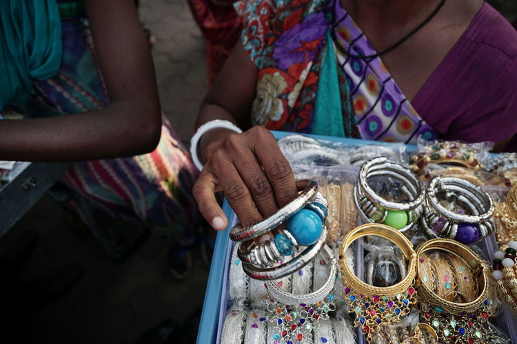 Midsection Of Woman Selling Bangles At Market