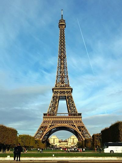Couple In Front Of Eiffel Tower Against Cloudy Sky