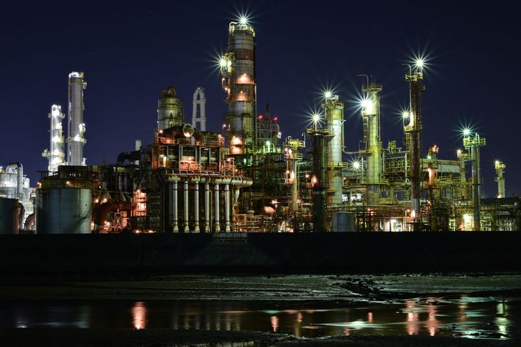 River Against Illuminated Factories At Night