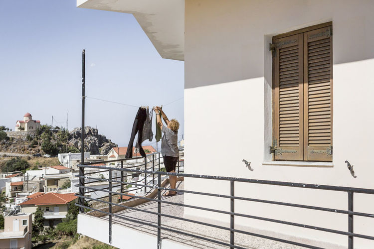 Rear View Of Woman Drying Clothes In Balcony