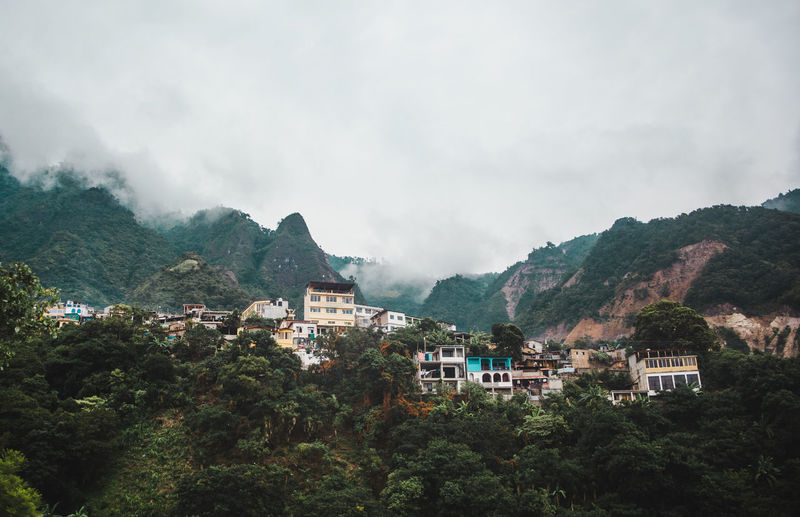 Buildings on mountain during foggy weather