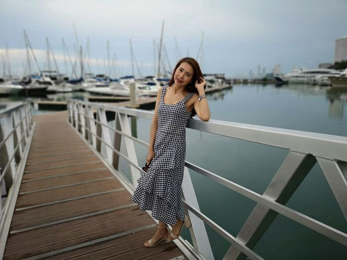 Portrait of smiling woman standing at harbor