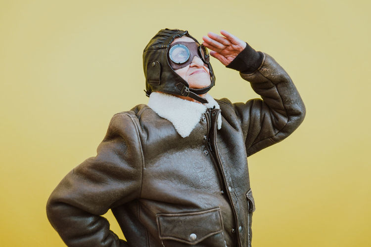 Senior woman wearing glasses while saluting against yellow background