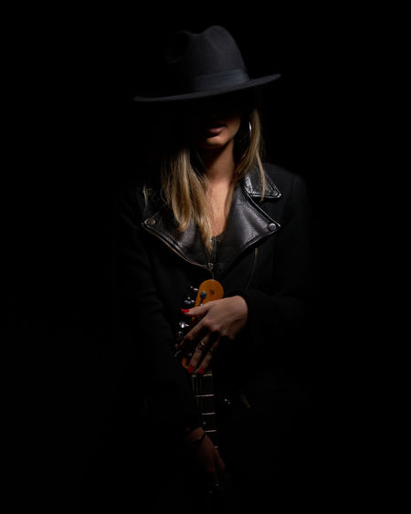 Female model wearing hat while holding guitar against black background