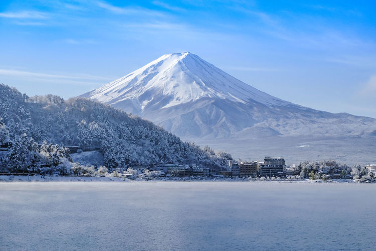 Mt Fuji with snow in winter at lake Kawaguchiko Japan Beauty In Nature Blue Cloud - Sky Cold Temperature Environment Landscape Mountain Mountain Peak Nature No People Scenics - Nature Sky Snow Snowcapped Mountain Tranquil Scene Volcano Water Winter