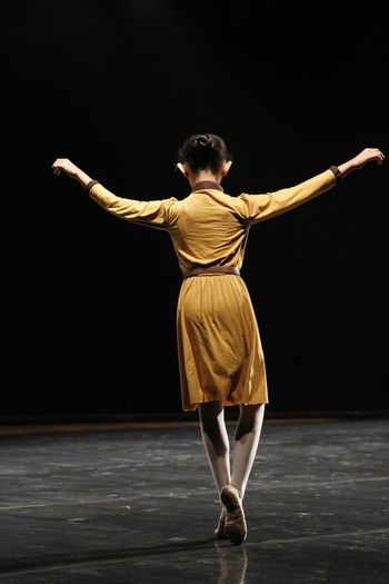 Rear view of full length of man dancing against black background