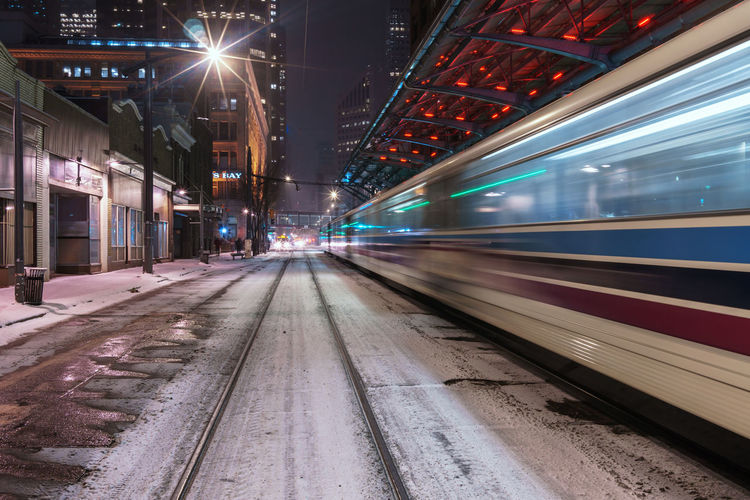 Blurred motion of train moving at railroad station platform during night