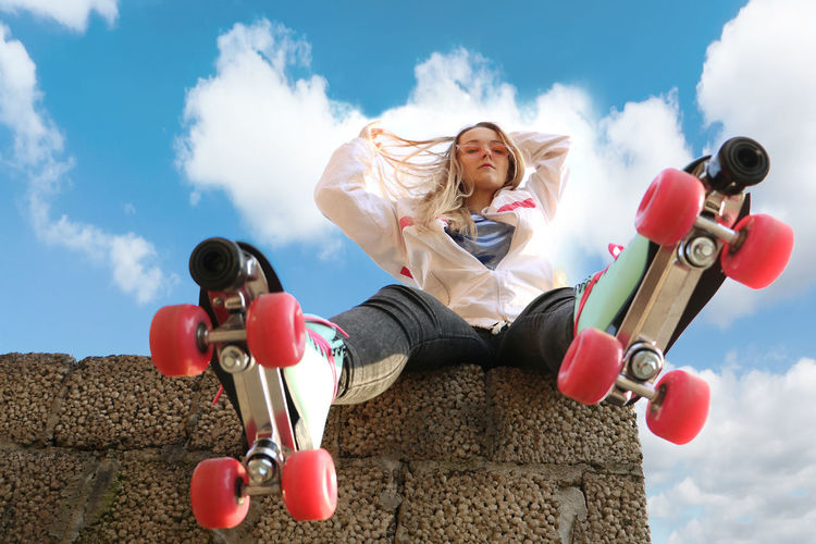 Young woman wearing roller skate against sky