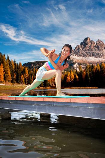 Woman standing on bridge at lake