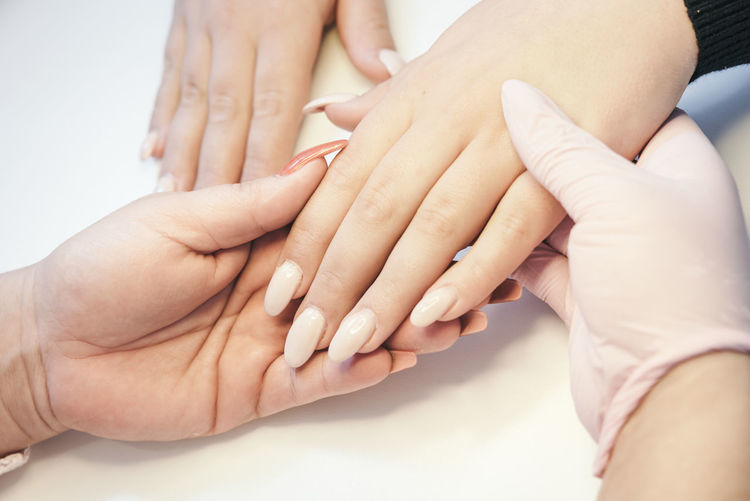 Cropped image of beautician holding hands at spa