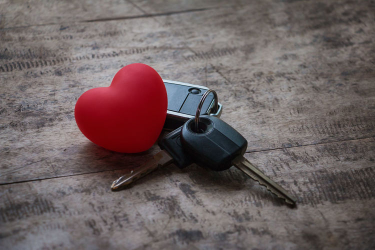 Close-up of red heart shape with car keys on table