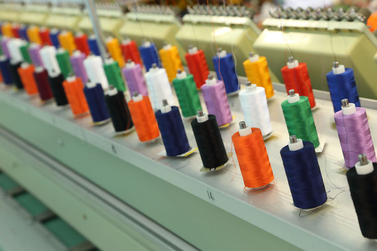 Machine Embroidery Sewing Textile Thread Industry Background Cotton Factory Manufacturing Clothing Threads Spool Reel Fashion Material Sew Tailor Colorful Polyester Craft Manufacture Bobbin Shop Clothes Fiber Fabric Color Wool SPOOLS Production Needle Work White Equipment Product Industrial Needlework Coil Orange Black Blue