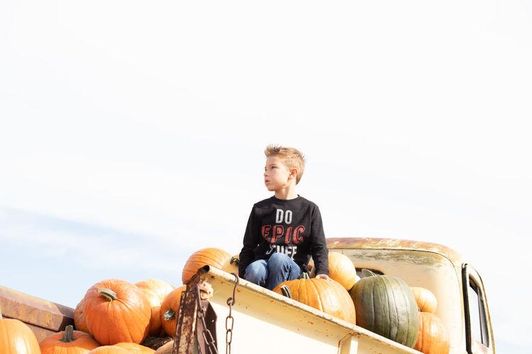 Low angel view of boy sitting on pumpkin in truck against sky