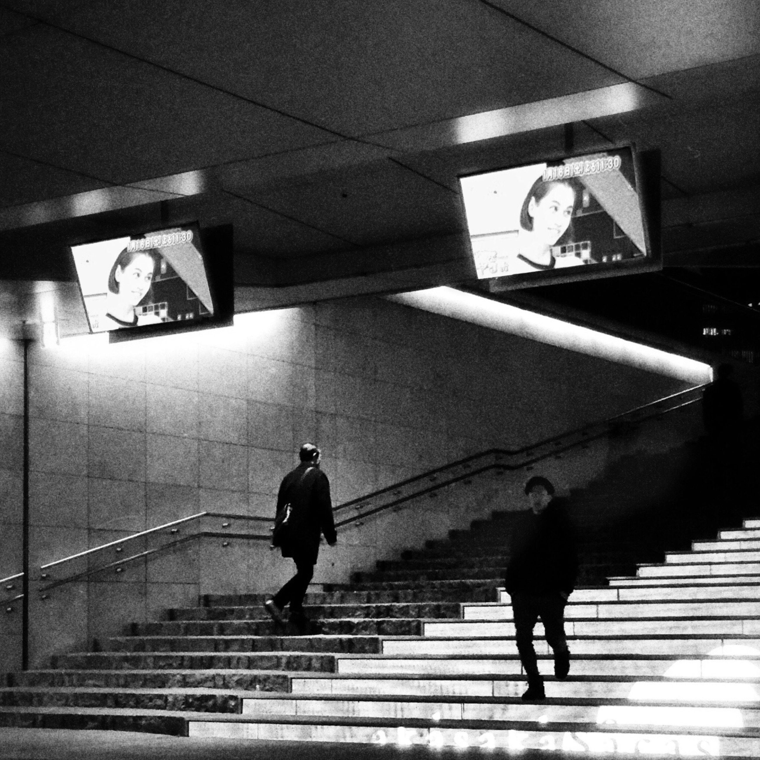 men, steps and staircases, full length, steps, lifestyles, indoors, staircase, railing, built structure, architecture, walking, illuminated, escalator, person, subway, leisure activity, rear view