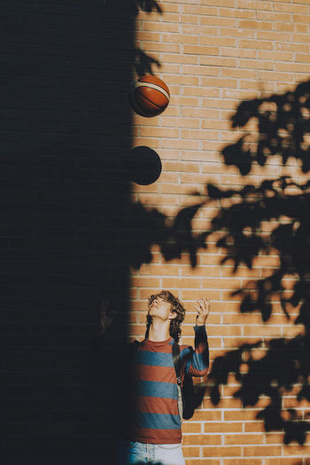 Shadow of woman standing against brick wall