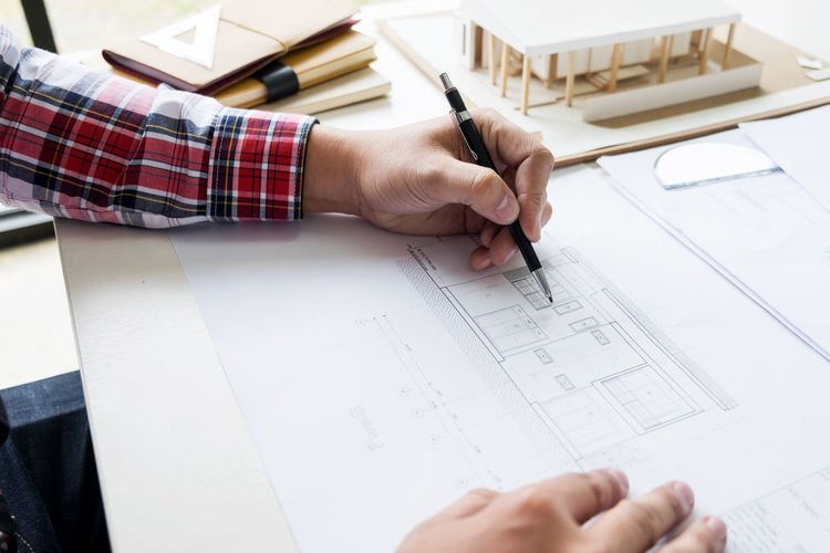 Cropped image of architect making blueprint in office
