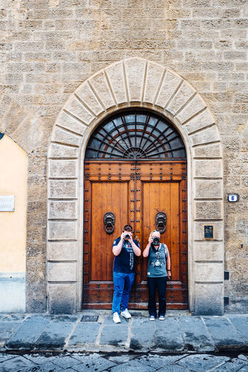 Full Length Of Man And Woman Photographing With Camera Against Wooden Door