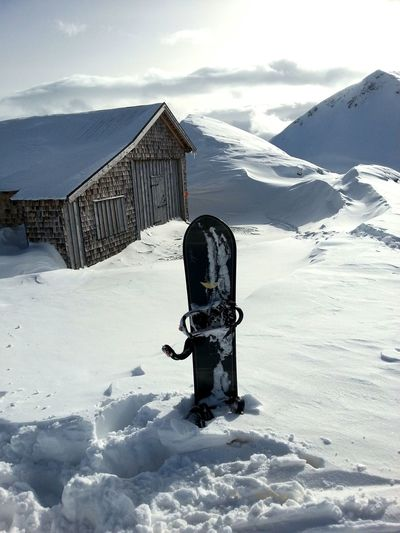 Snowboard sticking out from snow