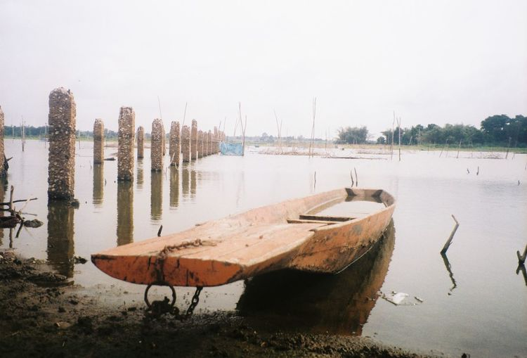 Boats moored on shore against sky