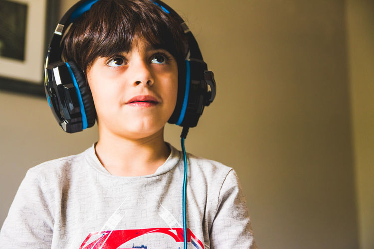 Boy looking away while wearing headphones at home