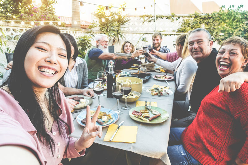 Happy family and friends taking selfie at barbecue dinner - Multiracial people having fun eating and drinking wine on patio house outdoor - Food and technology trend concept - Focus on asian girl face Smiling Group Of People Food And Drink Happiness Emotion Table Real People Women Lifestyles Drink Food Friendship Men Celebration Glass People Dinner Selfie Barbecue Family