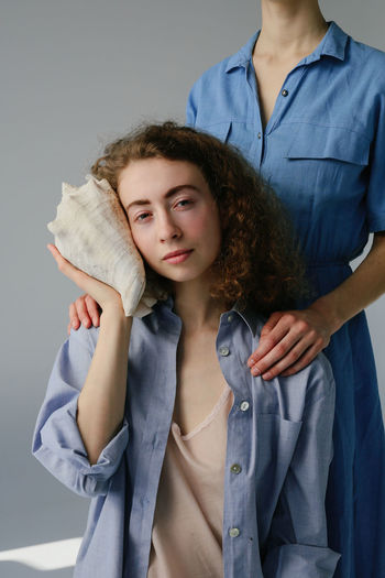 Women Two People People Portrait Females Real People Girls Studio Shot Hairstyle Care Togetherness Indoors  Front View Casual Clothing Family Positive Emotion Blue Sisters Sisterhood Casual Look Casual Females Portrait Of A Woman Curly Hair Curls Curly Dress Seashell Shell Face Hands Calm