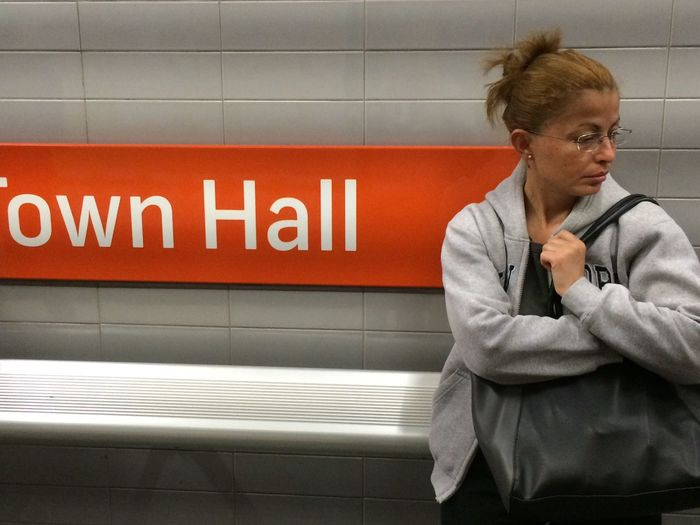 Woman Standing Against Text On Wall At Subway Station