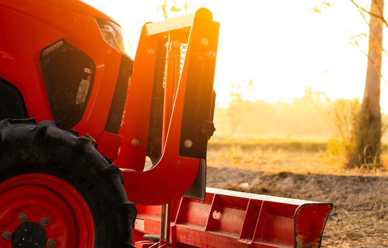 Close-up of tractor on field during sunset