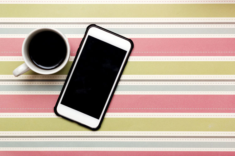 High Angle View Of Coffee By Mobile Phone On Table