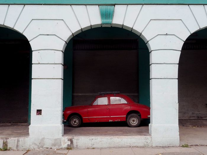 Architecture Built Structure Mode Of Transportation Transportation Land Vehicle Red Arch Building Exterior Motor Vehicle Car Day No People City Street Outdoors Building Parking Travel Stationary Old Architectural Column Garage Backgrounds Copy Space