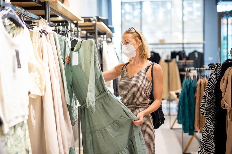Full length of woman looking at camera at store