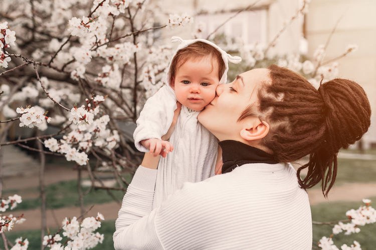 Side View Of Woman Kissing Cute Daughter In Park