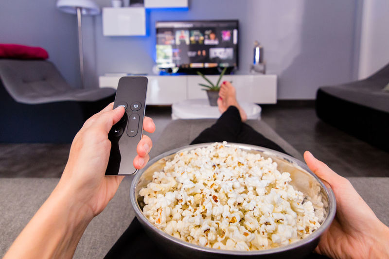 choosing a tv show with popcorn Apple Tv Remote Bowl Couch Device Screen Focus On Foreground Food Home Interior Human Body Part Human Hand Indoors  Personal Perspective Remote Television Tv Watching Tv